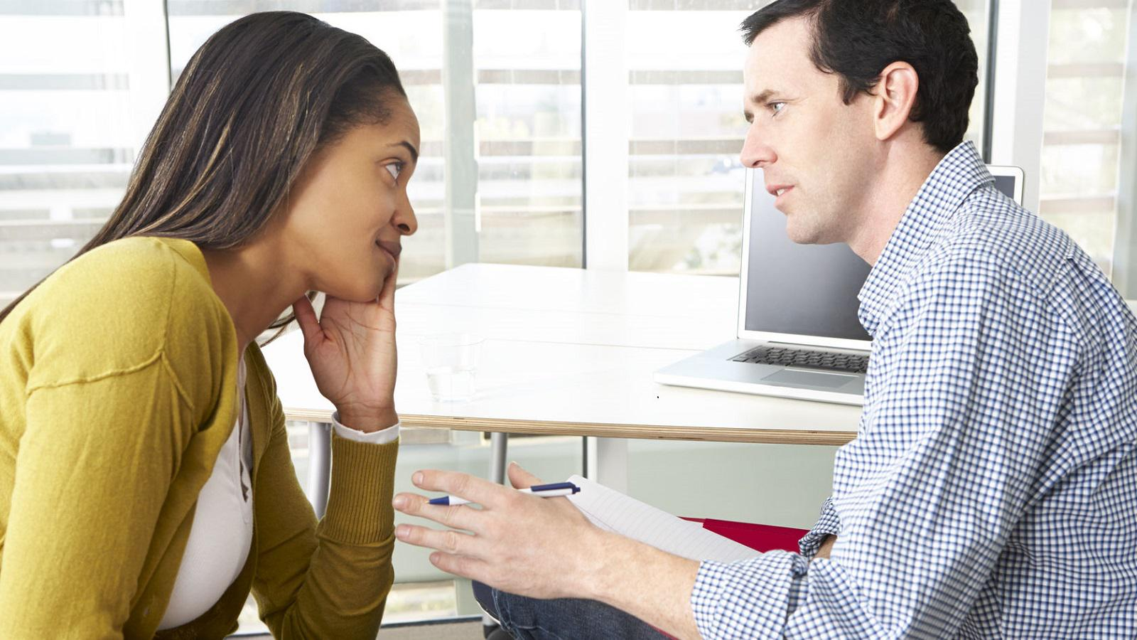 A man in a checkered shirt speaks to a woman in a sweater. Text says Find specialized treatment programs and supportive services.