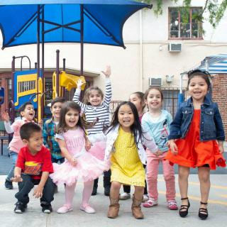A group of children smiling and laughing on a playground.