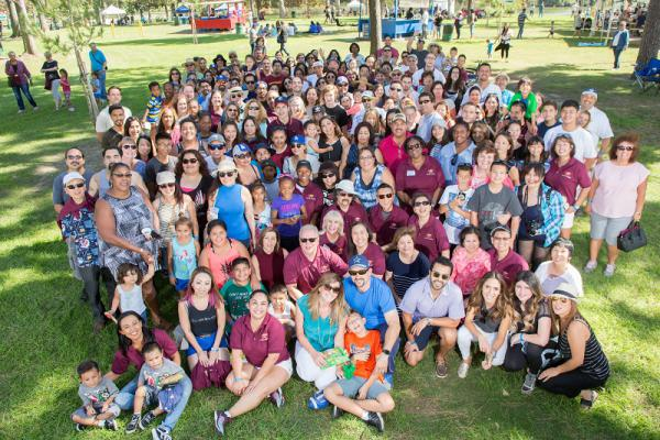 Large group of Pacific Clinics' employees and their families posing in a park.