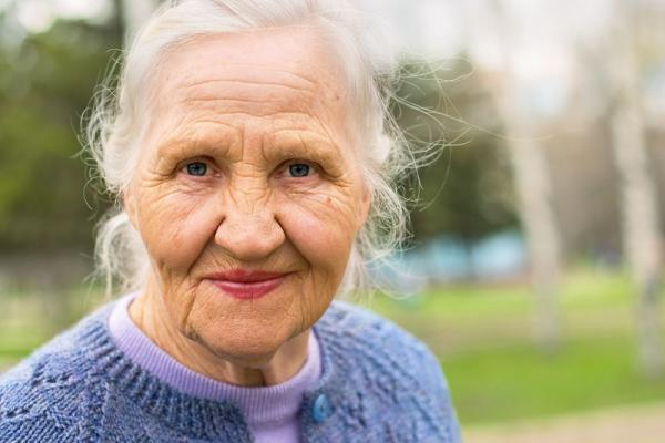 Older adult looking ahead with a small smile.