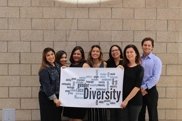 Recovery Education Institute staff holding up a sign encouraging diversity.