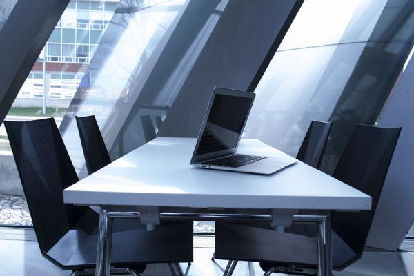 An empty conference room with chairs around a table with a laptop open on top.