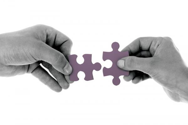 Two hands holding puzzle pieces close together.
